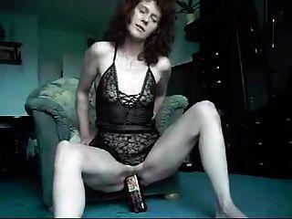 परिपक्व महिला एक व्हिस्की की बोतल निगल